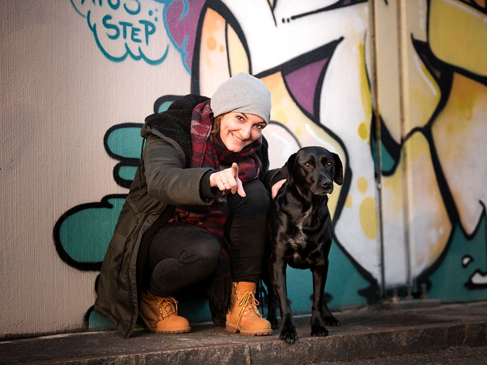 Franziska sitzt mit ihrem Hund Ida vor einer farbigen Wand